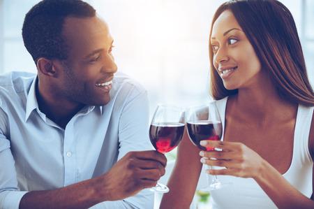Wir feiern ihren besonderen Tag. Schöne junge afrikanische Paar nahe beieinander und hält Weingläser sitzen