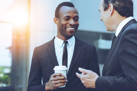 Koffiepauze. Twee vrolijke zaken mannen praten terwijl een van hen de koffiekop