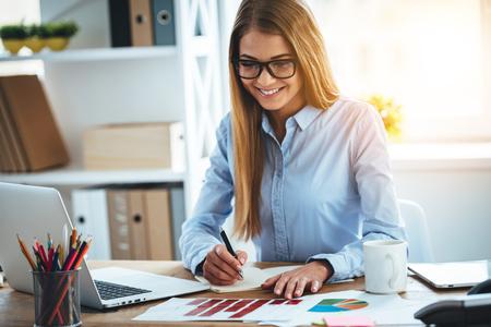 mujer trabajadora: Experto en su negocio. Alegre joven y bella mujer que hace algunas notas en el cuaderno y mirando a los gráficos con sonrisa mientras está sentado en su lugar de trabajo