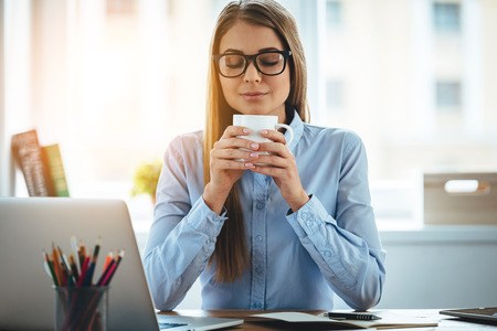 vrouwen: Lekkere koffie! Jonge mooie vrouw bedrijf koffiekopje en het houden van de ogen gesloten tijdens de vergadering op haar werkplek Stockfoto
