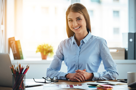 Toothy smile from real expertise. Cheerful young beautiful woman looking at camera with smile while sitting at her working place Stok Fotoğraf