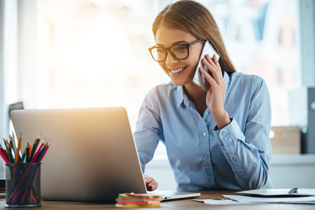 Yes I see your email! Cheerful young beautiful woman in glasses talking on mobile phone and using laptop with smile while sitting at her working place Imagens