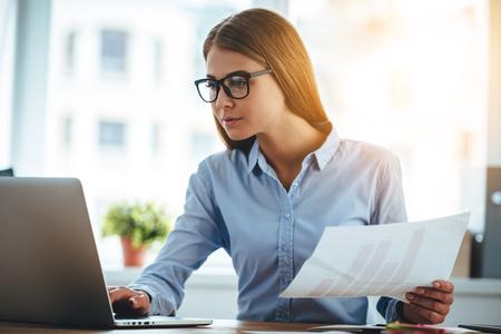 Duplo controlo tudo. Mulher bonita nova nos vidros usando o computador portátil e titulares de documentos enquanto está sentado em seu lugar de trabalho