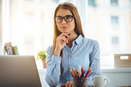 mujer trabajadora: Nuevo día nuevas decisiones. Pensativo mujer hermosa joven con la mano en la barbilla y mirando reflexivo mientras está sentado en su lugar de trabajo