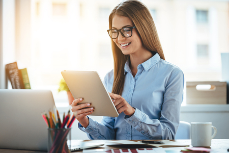 Lets check my timetable! Cheerful young beautiful woman in glasses using her touchpad with smile while sitting at her working place Stock Photo