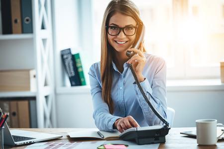 Voy a conectar en un segundo! Alegre mujer joven y bella en copas hablando por teléfono y mirando a la cámara con una sonrisa mientras está sentado en su lugar de trabajo