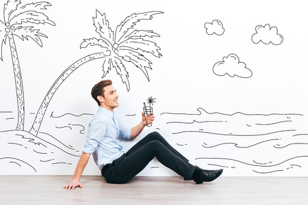 stubble: Dreaming about vacation. Young handsome man holding drawn cocktail and looking away with smile while sitting on the floor with illustration of resort in the background