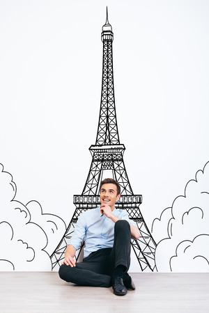 toothy smile: Dreaming about Paris. Young handsome man keeping hand on chin and looking away with smile while sitting on the floor with illustration of Eiffel Tower at the background