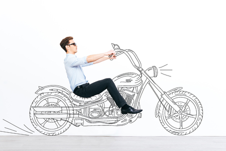 handsome young man: Catch him if you can! Handsome young man driving drawn motorcycle against white background