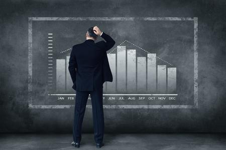 Harte Entscheidungen jeden Tag. Rückansicht des reifen Geschäftsmann kratzte sich am Kopf, während er gegen grauen Hintergrund mit Abbildung des Diagramms