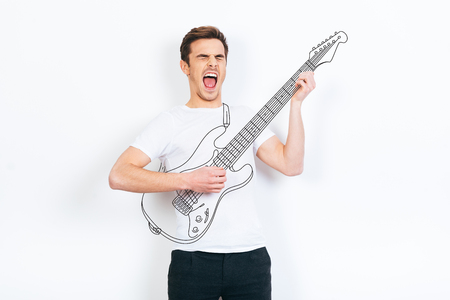 handsome young man: Like a rock star. Young handsome man playing drawn guitar and keeping mouth open while standing against white background