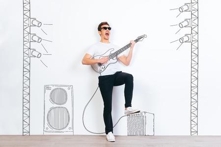 ¡Estrella de rock! Hombre hermoso joven en gafas de sol tocando la guitarra dibujada y mantener la boca abierta mientras está de pie contra el fondo blanco con la ilustración de la columna de música y luz de la etapa
