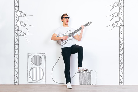 Rock star! Young handsome man in sunglasses playing drawn guitar and keeping mouth open while standing against white background with illustration of stereo column and stage light Stock Photo