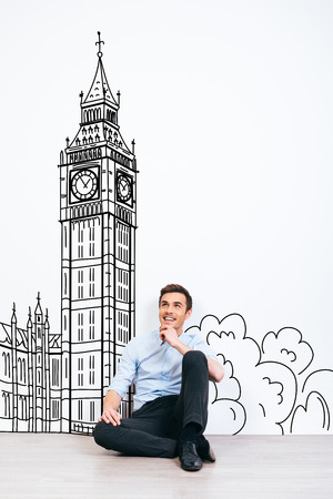 day dreaming: Dreaming about London. Young handsome man keeping hand on chin and looking away with smile while sitting on the floor with illustration of Big Ben at the background