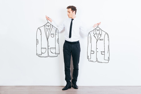 handsome young man: What jacket shall I choose?  Handsome young man choosing between two drawn jackets while standing against white background