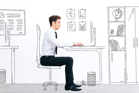 stubble: New working day. Side view of handsome young man working with drawn computer while sitting at his illustrated working place