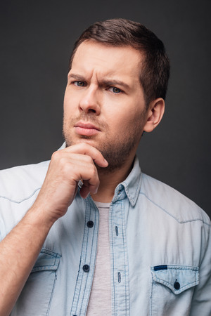 What do you mean? Handsome young man keeping hand on chin and looking at camera while standing against grey background Stock Photo