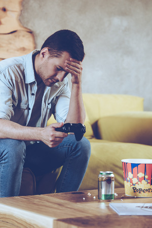 Perdido la batalla. joven desesperado celebración de joystick y mantener su mano en la frente mientras se está sentado en el sofá en casa