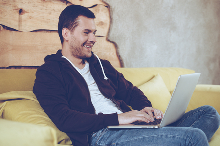 net surfing: Surfing net at home. Cheerful young man using his laptop with smile while sitting on couch at home