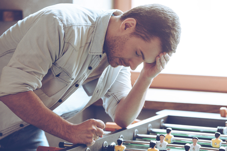 looser: Looser. Desperate young man keeping his hand on forehead while standing over foosball in front of window Stock Photo