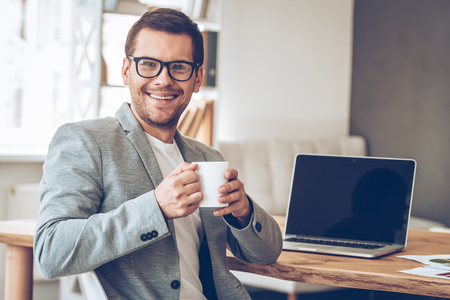 Coffee break. Handsome young man in glasses holding coffee cup and looking at camera with smile while sitting at his working place