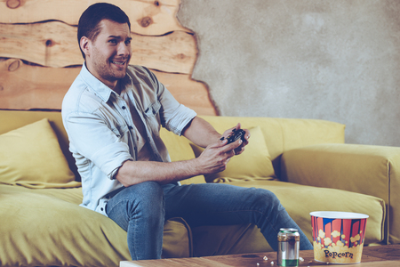 playing video game: Just one more lap! Cheerful young handsome man playing video game and looking excited while sitting on the couch at home