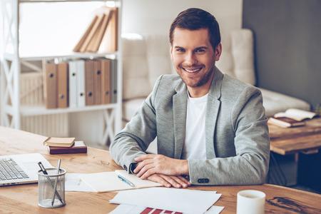 Vrije werkdag. Vrolijke knappe jonge man die camera kijkt met glimlach terwijl hij op zijn werkplek zit
