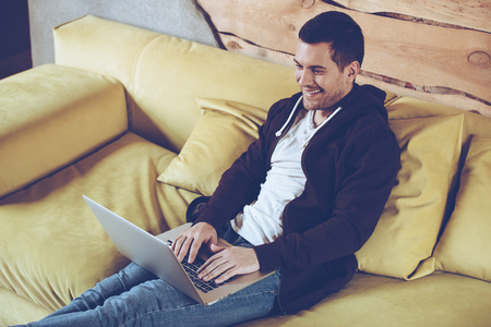 hooded top: Surfing the net. Top view of cheerful young man using his laptop with smile while sitting on couch at home