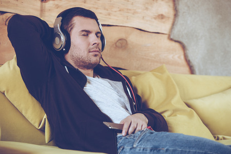home keeping: Great song! Young man in headphones keeping eyes closed while sitting on couch at home Stock Photo