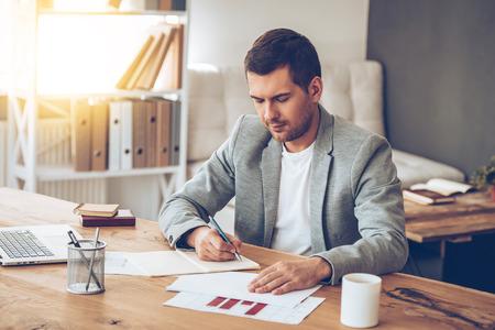 hombre escribiendo: La creatividad en el trabajo. joven apuesto hombre pensativo escribiendo en su portátil mientras está sentado en su lugar de trabajo