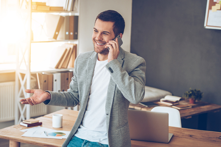 casual office: See you in my office! Handsome young man talking on mobile phone with smile while leaning to the table at his office Stock Photo