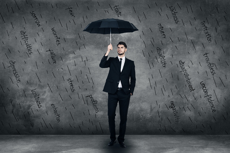 full length: Feeling protected. Full length of confident young man in full suit holding umbrells while standing in front of the concrete wall