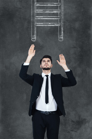 outstretched: Helping ledder. Handsome young man in formalwear stretching out his hands and looking up while standing against chalkboard with drawing ledder on it Stock Photo