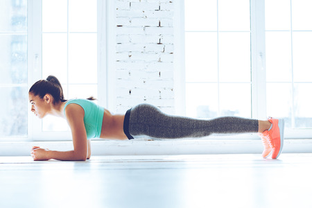 Perfect plank. Full-length side view of young beautiful woman in sportswear doing plank while standing in front of window at gym