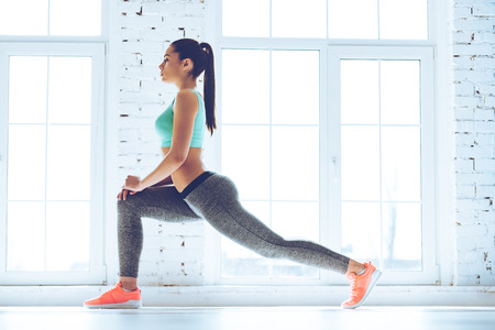 Warming up before training. Side view of young beautiful young woman in sportswear doing stretching while standing in front of window at gym Imagens