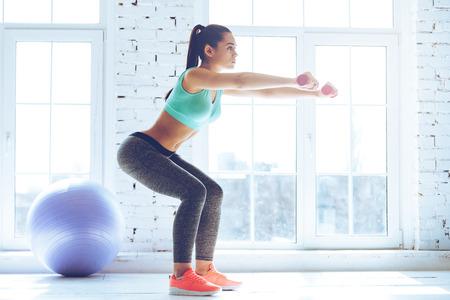 sentadilla profunda. Vista lateral de la joven y bella mujer en ropa deportiva haciendo cuclillas y la celebración de pesas mientras está de pie delante de la ventana en el gimnasio