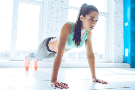 How long can you hold a plank? Full length of young beautiful woman in sportswear doing plank while standing in front of window at gym Stok Fotoğraf