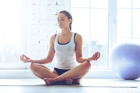 namaste: Namaste! Young beautiful young woman keeping eyes closed while sitting in lotus position in front of window at gym Stock Photo