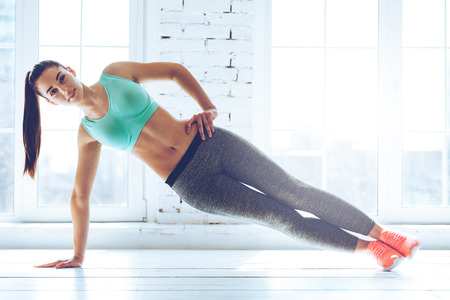 Perfect side plank. Full length of young beautiful woman in sportswear doing side plank and looking at camera in front of window at gym