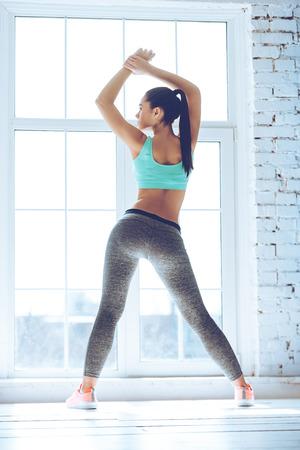 Calentando. Vista trasera de la joven y bella mujer joven en ropa deportiva haciendo estiramiento mientras está de pie delante de la ventana en el gimnasio