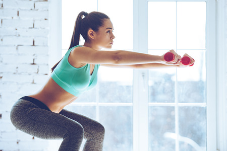 Feel the burn in buttocks. Side view of beautiful young woman in sportswear doing squat and holding dumbbells while standing in front of window at gym Stock Photo
