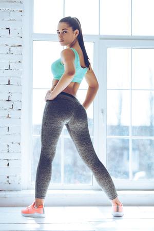 Listo para la gran entrenamiento! Vista trasera de una mujer joven y bella mujer en ropa deportiva mirando a la cámara sobre el hombro mientras está de pie delante de la ventana en el gimnasio