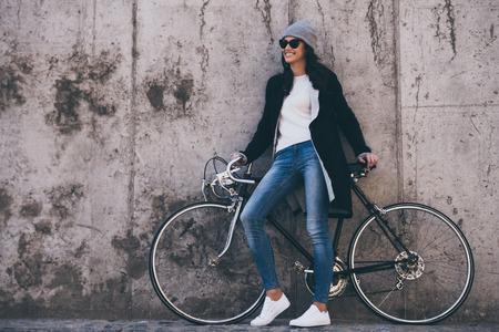 Dat was een geweldige rit! Mooie jonge vrouw in zonnebril die handen op haar fiets houden en weg met glimlach terwijl in openlucht status tegen concrete muur kijken