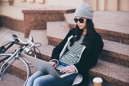 persona sentada: blogger moderna en el trabajo. Joven y bella mujer en gafas de sol con su ordenador portátil mientras está sentado en medidas al aire libre Foto de archivo