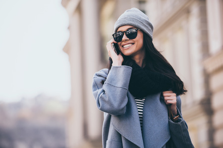 So nice to here you! Beautiful young woman in sunglasses talking on mobile phone and looking away with smile while walking outdoors