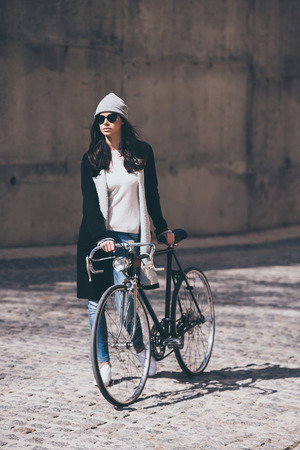 style woman: Enjoying the urban lifestyle. Full length of beautiful young woman in sunglasses rolling her bicycle and looking away while walking outdoors Stock Photo