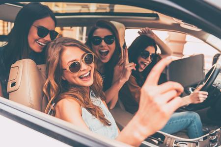 ¡Hora de hacerse un selfie! Vista lateral de cuatro hermosas mujeres alegres jóvenes que hacen autofoto y sonriendo mientras estaba sentado en el coche juntos