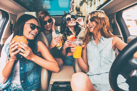 take out food: Enjoying their lunch in the car. Four beautiful young cheerful women looking at each other with smile and eating take out food while sitting in car