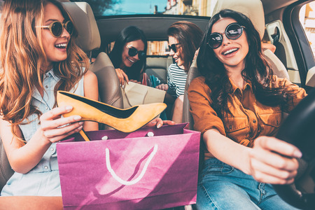 Next stop is lingerie shop! Four beautiful young cheerful women holding shopping bags and looking at each other with smile while sitting in car Stok Fotoğraf
