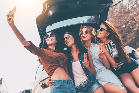 Sólo una autofoto antes de viaje por carretera! Cuatro hermosas mujeres jóvenes alegres que hacen autofoto con una sonrisa mientras está de pie cerca del tronco del coche